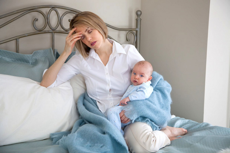 tired mother in bed with a baby
