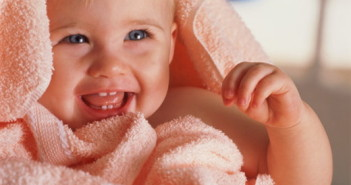 Baby (6-9 months) wrapped in towel smiling, close-up