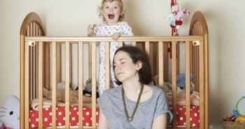 The author, with closed eyes, and cheering baby in cot