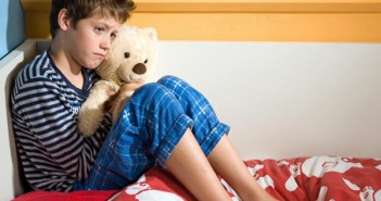 young-boy-on-bed-with-teddy-bear