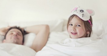 little-girl-laying-in-bed-with-her-father-1
