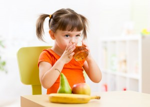 Smiling girl sitting on the table with fruits and juice