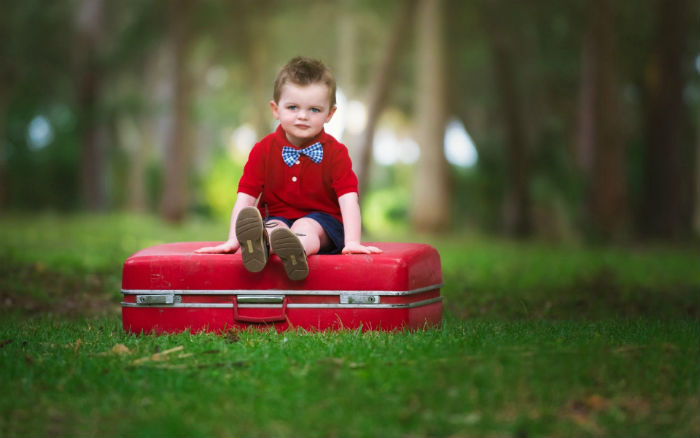 Cute-Baby-Boy-Sitting-On-Suitcase-Wallpaper